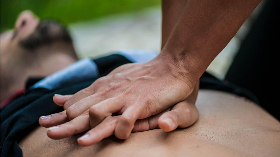 Un homme est couché sur le dos pendant que quelqu'un pratique la RCR sur sa poitrine