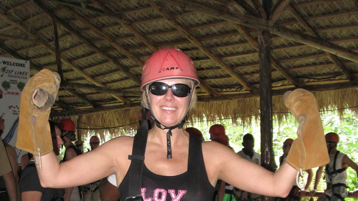 Beth Luhowy, le sourire aux lèvres, porte fièrement un casque rose et un harnais de sécurité.