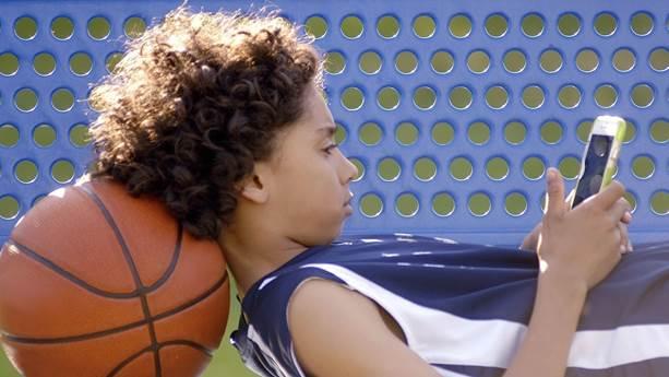 Boy avec le basket text sur son téléphone