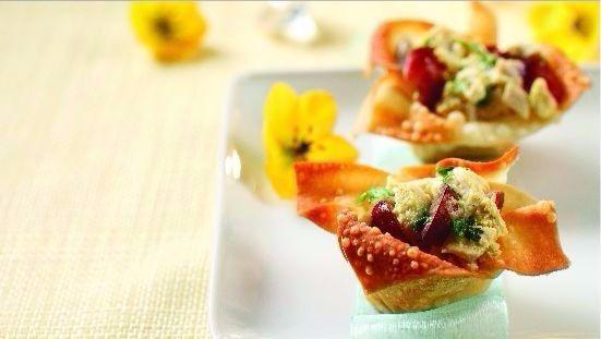 Salade de poulet au cari dans une tasse de wonton sur une plaque blanche avec des fleurs jaunes