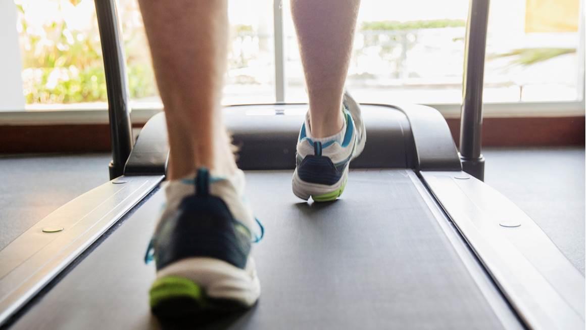 Gros plan des pieds d'un homme qui court sur un tapis roulant.