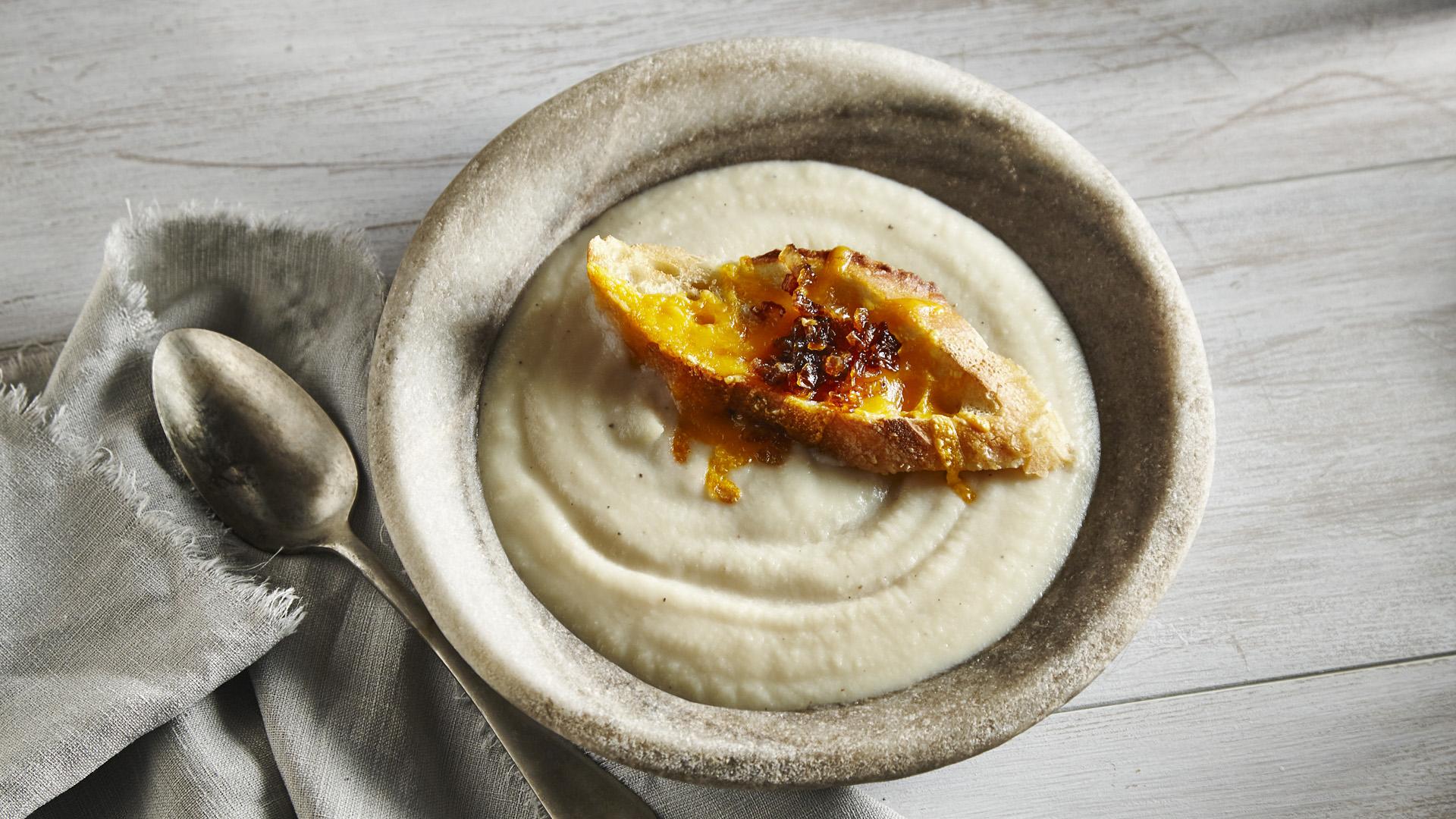 Bol de soupe de céleri-rave à la crème garnie de baguette au fromage croustillant
