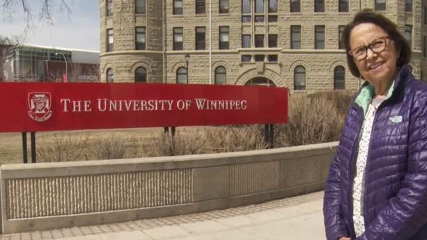 Esther Sanderson sourit, habillée d'une veste violette, à côté d'un panneau de l'Université de Winnipeg.