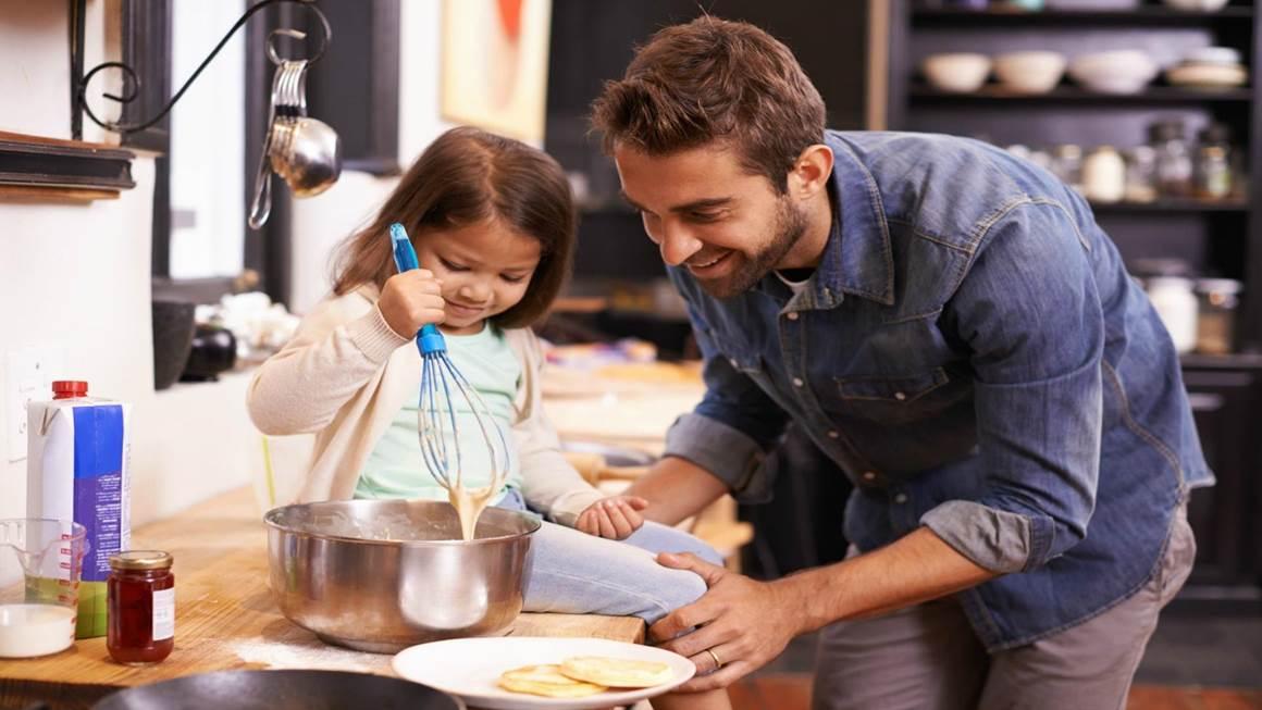 Un père et une fille sourient en cuisinant ensemble sur le comptoir de la cuisine.