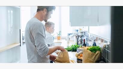 Dans une cuisine, un père et son fils rangent des articles d'épicerie.
