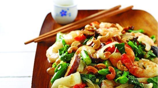 Crevettes, bok choy, poivrons rouges, noix de cajou sur planche de bois avec des baguettes