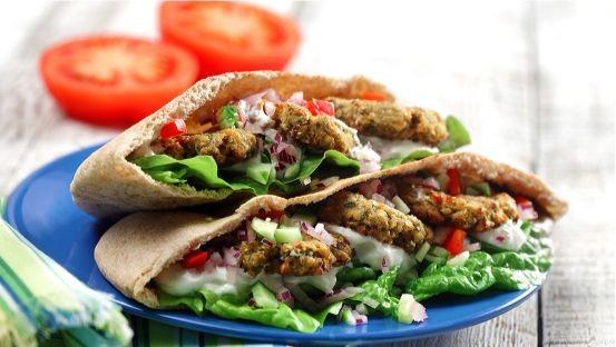 Pain pita rempli de falafel, de laitue, de tzatziki, de tomates, d'oignon et concombre