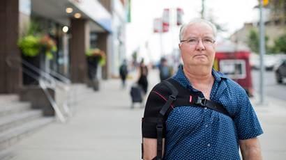 Paul Morse marche dans la rue avec une canne.