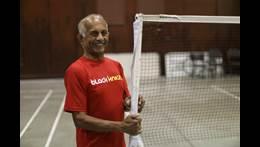 Jerry porte un t-shirt rouge à côté d'un filet de badminton dans un gymnase.