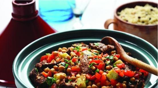 Bol rempli de pois chiches, d'agneau, de tomates hachées, de couscous et de persil