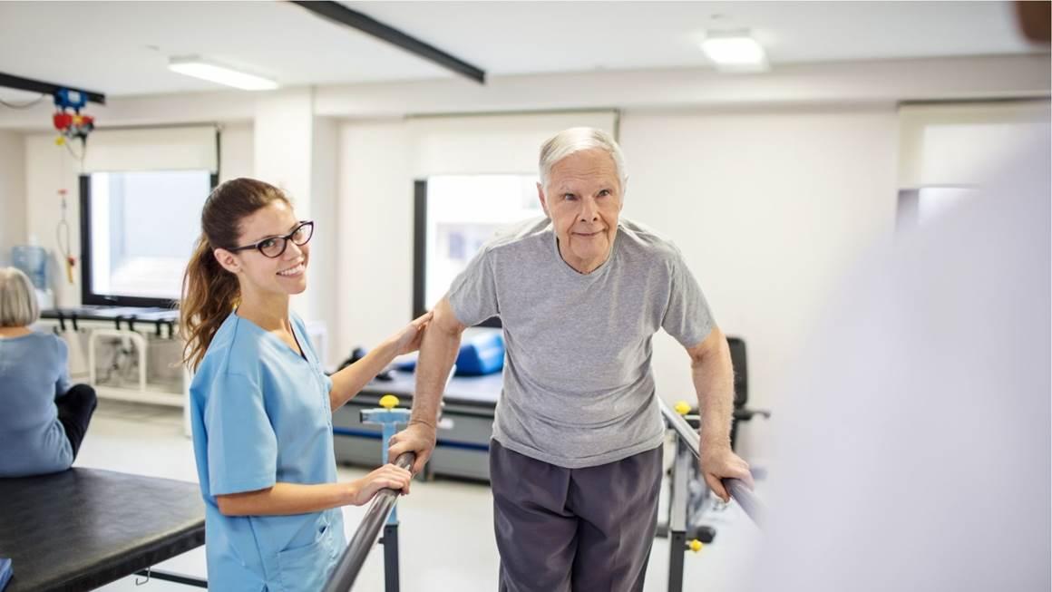 Une infirmière assistant un patient en réadaptation à marcher sur une plate-forme en pente.