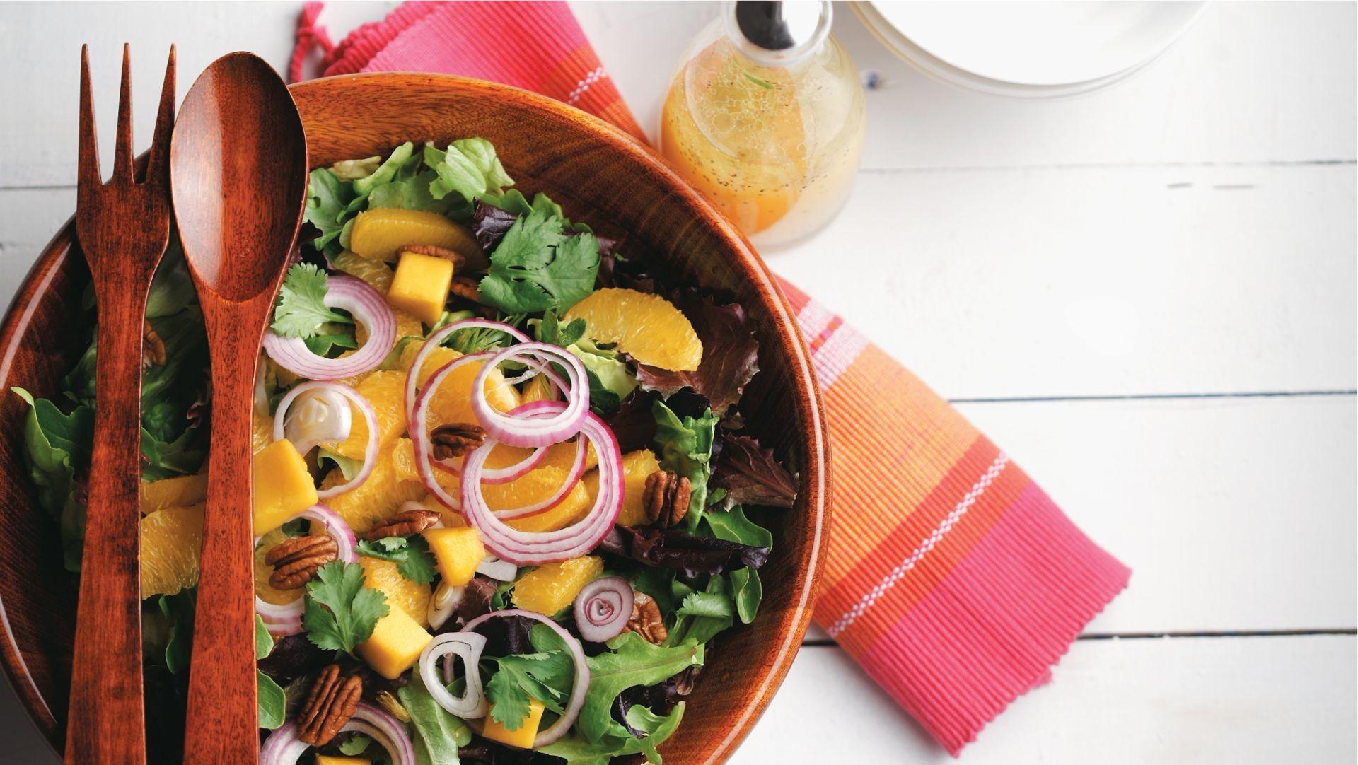 Salade de mesclun, mangue et noix de pacane dans un bol de bois avec utensiles de bois.