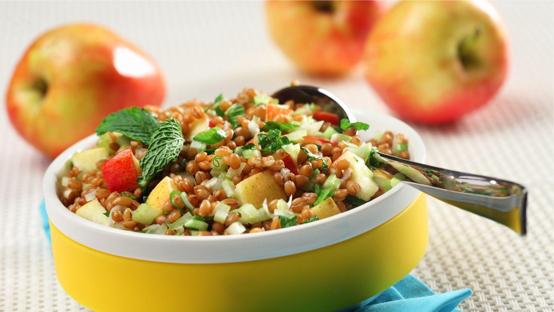 Salade aux grains de blé et pommes dans un bol jaune sur une serviette bleue