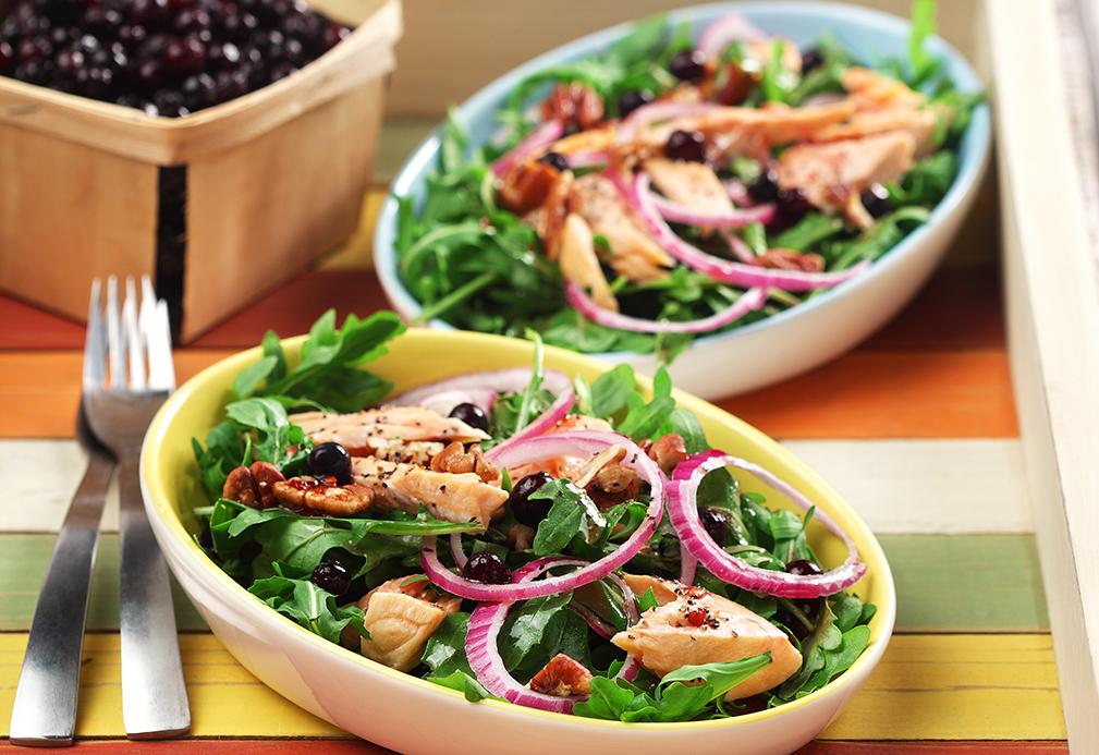 Bol de salade verte, saumon cuit, oignon et baies fraîches
