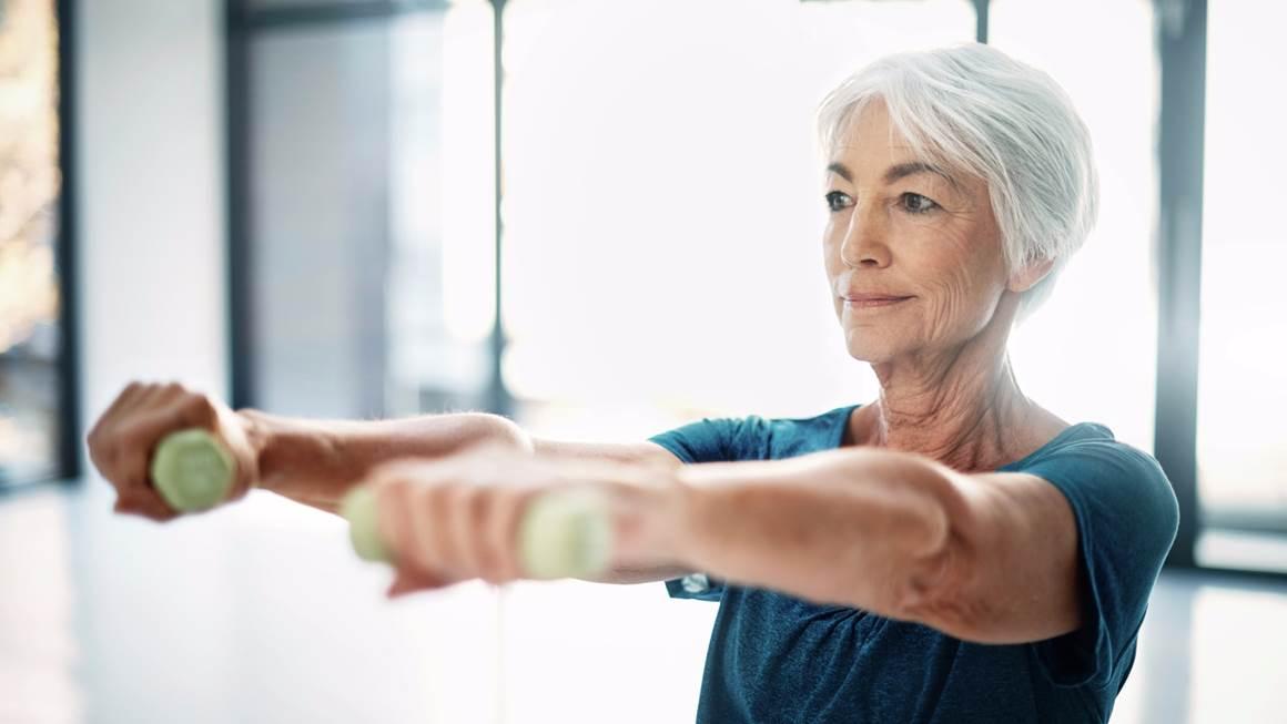 Une femme aux cheveux blancs soulève les poids