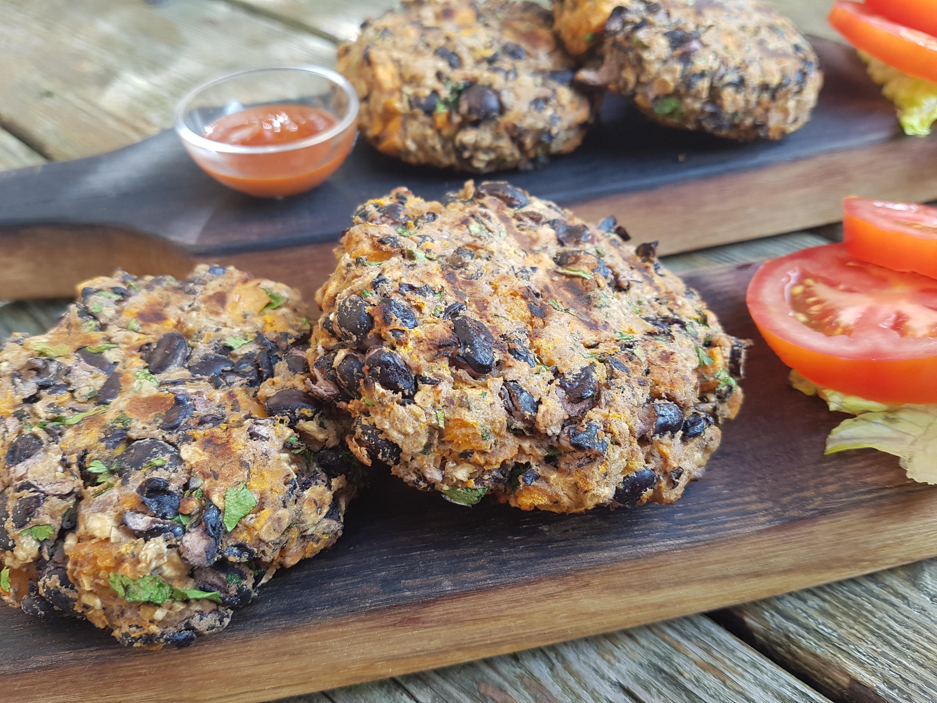 Galettes de hamburger de patates douces et de haricots noirs sur une planche avec des tomates