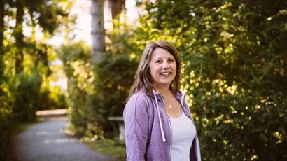 Tracy Bawtinheimer porte une veste violette en marchant dans un foret.