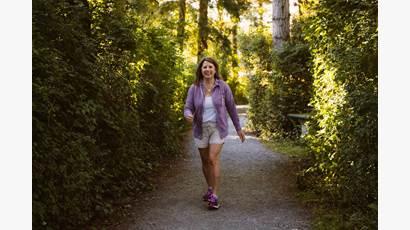 Tracy Bawtinheimer marche en forêt vêtue d'une veste mauve et de pantalons courts.