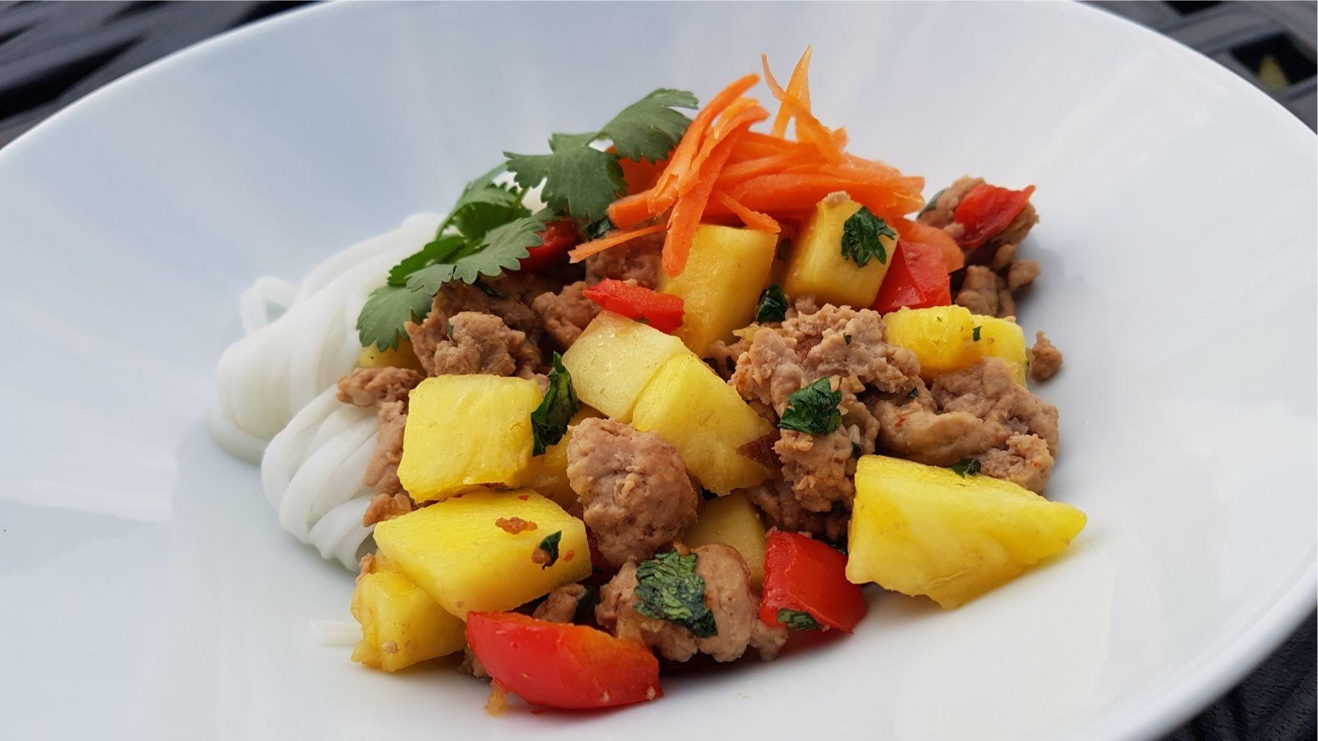 Bol de nouilles, dinde hachée, ananas, poivrons rouges et carottes râpées