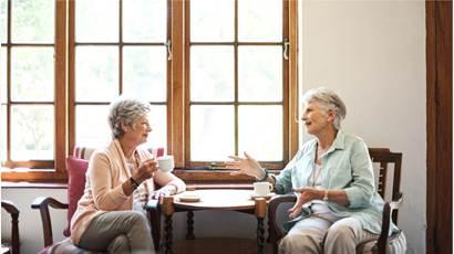 Deux femmes âgées parlent en prenant le thé