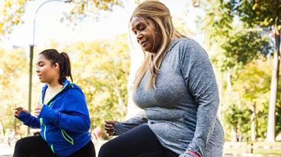 Deux femmes qui font des mouvements brusques sur un banc de parc en plein air