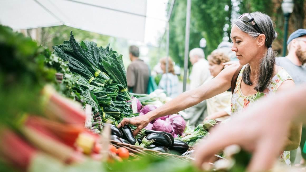 Femme achetant des légumes au marché des agriculteurs
