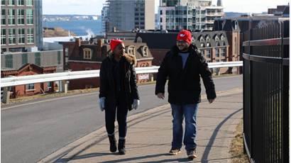 Deux bénévoles portant une tuque rouge marchent sur une rue principale.