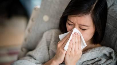 Une femme portant un chandail gris se mouche dans un mouchoir.