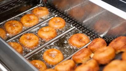 Une douzaine de beignes en train de frire dans l'huile.
