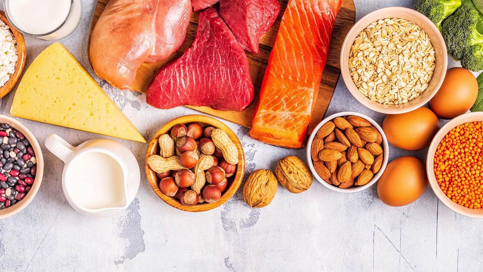 Un coup d'œil sur des ingrédients crus tels que des œufs, du saumon, du poulet, des graines, du lait, de la viande, du fromage, des amandes et des haricots.