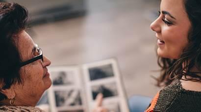 Une grand-mère et sa petite-fille qui parlent en regardant un album photo.