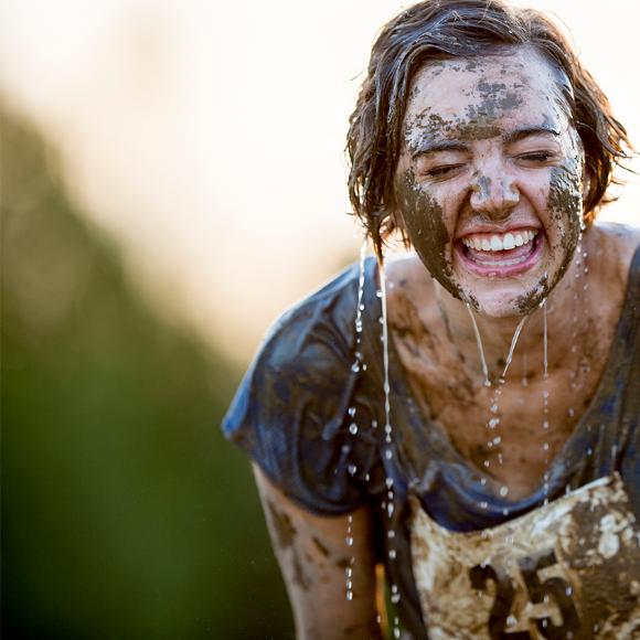 Une femme couverte de boue rit aux éclats durant une course à obstacles.