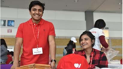 Un homme portant un t-shirt rouge et une femme arborant une chemise à carreaux rouge sourient et se tiennent derrière une table lors d'une activité