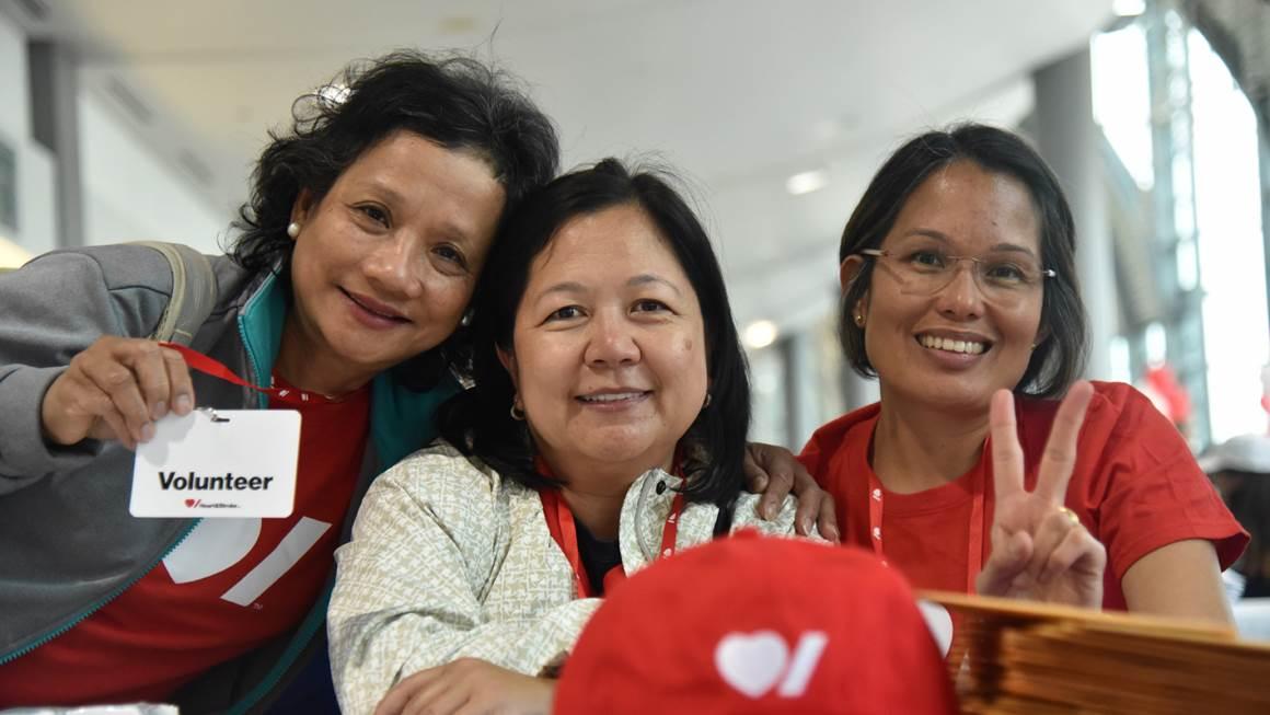 Trois femmes souriantes portant des vêtements au logo de Cœur + AVC.