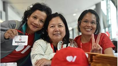 Trois bénévoles souriants portent un t-shirt de Cœur + AVC.