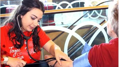 Une femme portant un t-shirt rouge se sert d'un stéthoscope.