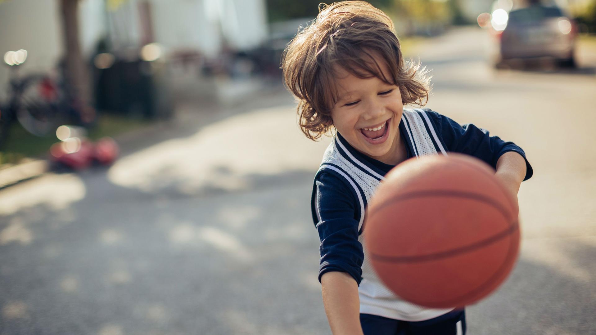 Boy-rebondissant-basket-ball-dehors