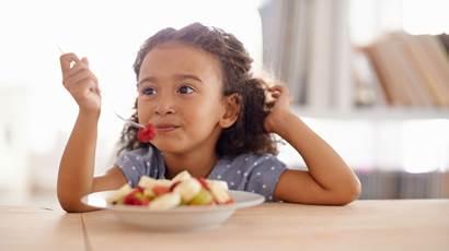 Fille de manger une salade de fruits