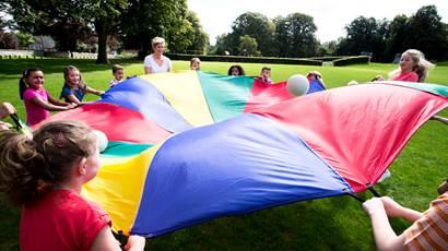 Les enfants et les enseignants jouant avec parachute coloré extérieur