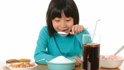 Une fille souriante prétend manger une grande cuillerée de sucre d