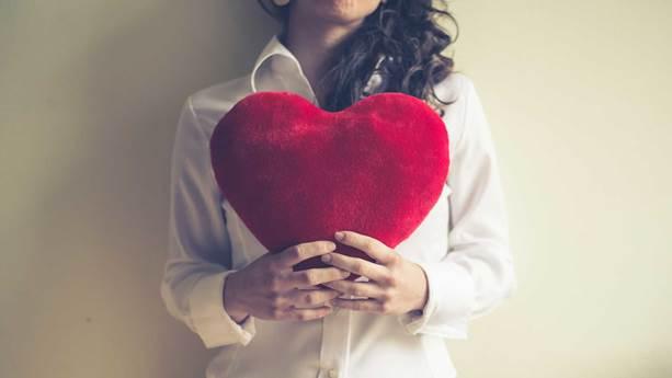 Femme, tenant coeur en peluche rouge devant sa poitrine