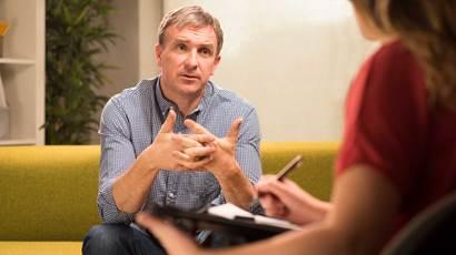 Man assis sur le divan parlant thérapeute