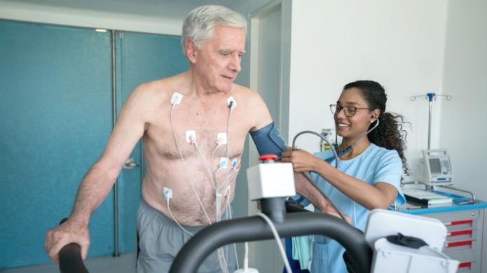 Une infirmière mesurant la pression artérielle d'un patient sur un tapis roulant.