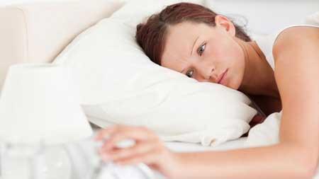 femme rousse couché dans le lit d'éteindre un réveil dans sa chambre