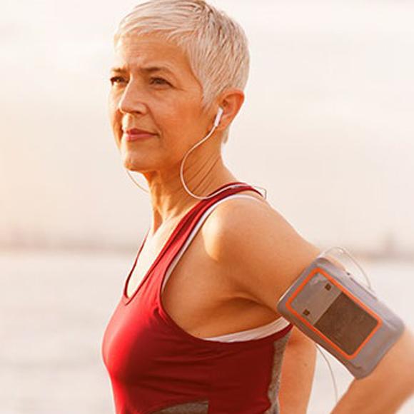 Une femme âgée porte un haut athlétique rouge avec un portable attaché à son bras.