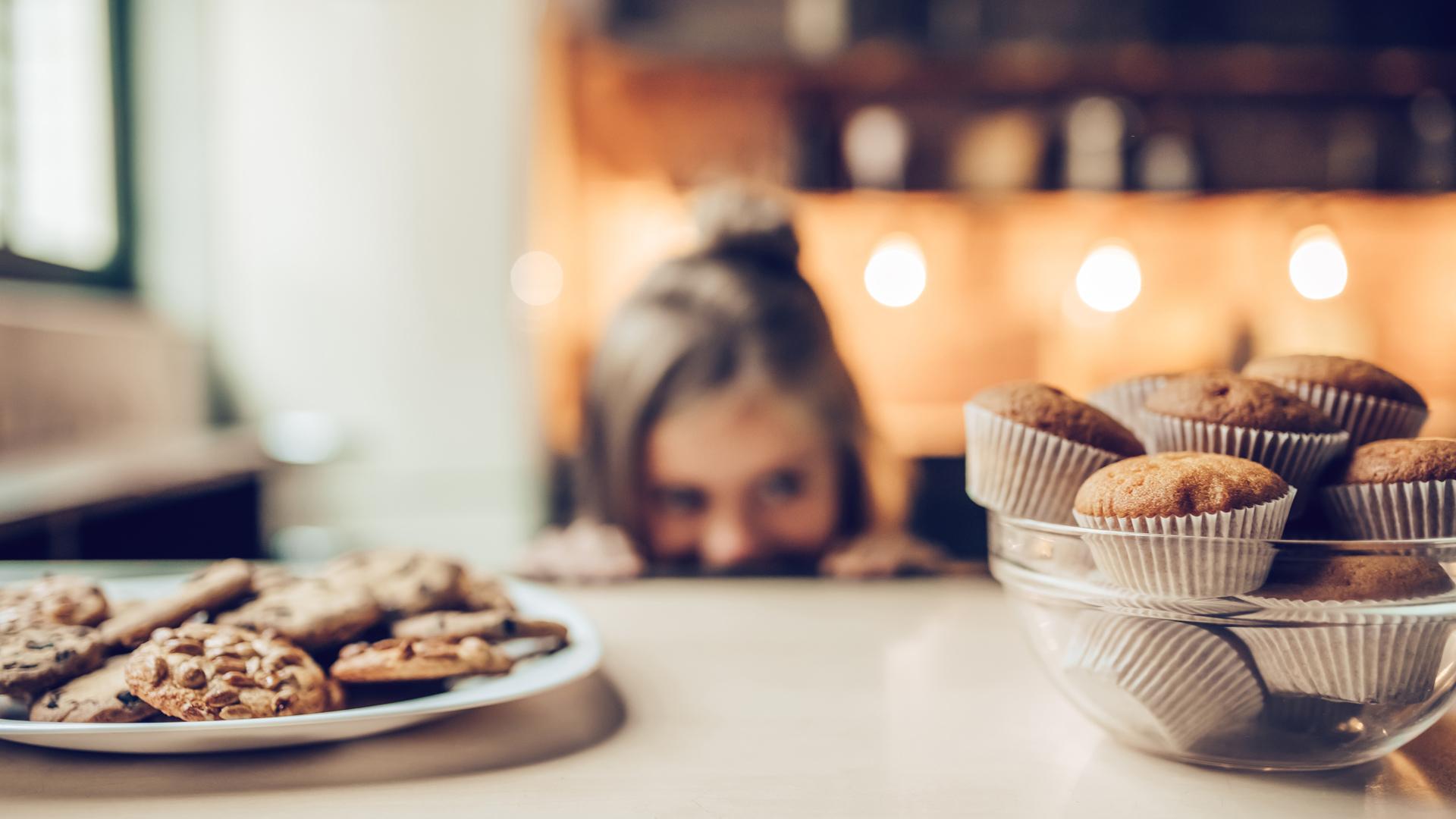 Une assiette de biscuits et un bol de muffins sont fixés du regard par une fillette en arrière-plan.