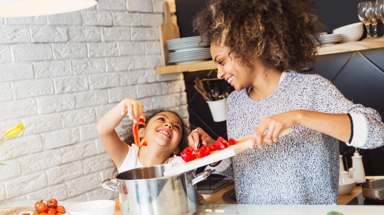 Une femme et sa fille apprêtant des légumes dans la cuisine.