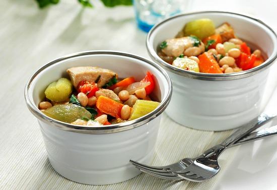 Deux bols blancs remplis de poulet cuit, de carottes, de céleri, de haricots blancs et de bouillon