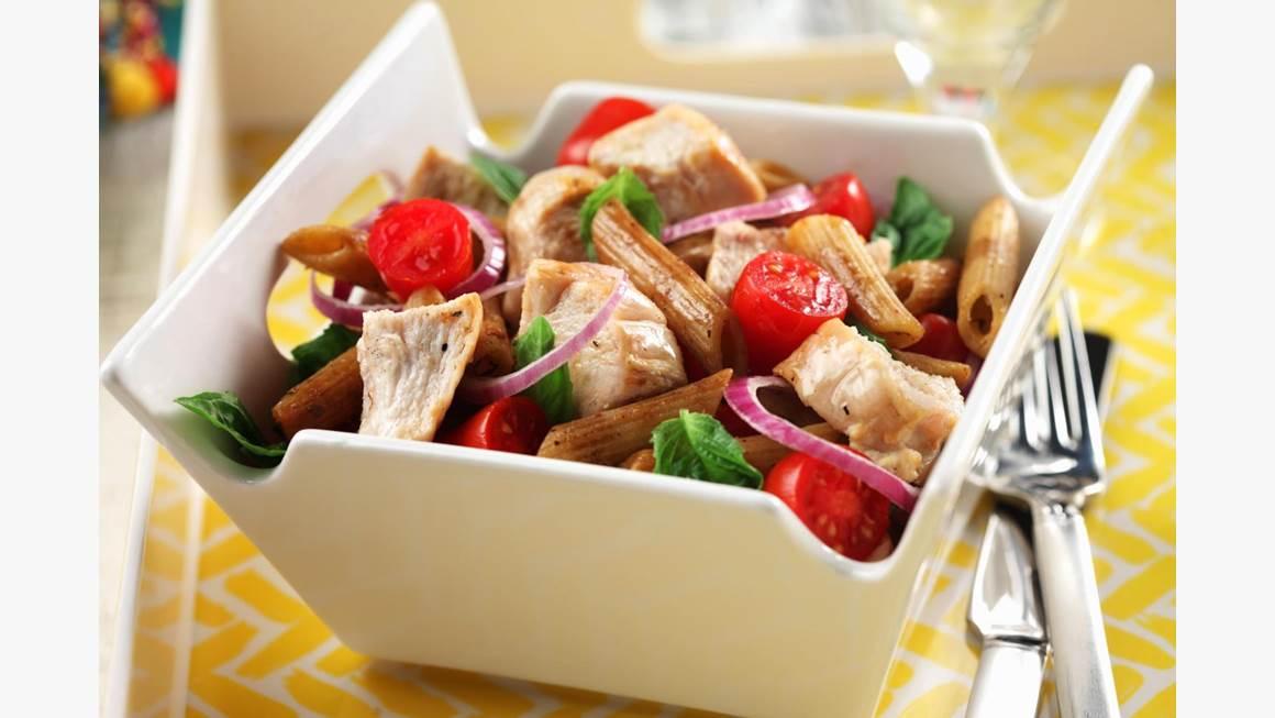 Salade de pâtes au poulet bistro dans un bol carré blanc avec une fourchette sur une nappe jaune