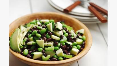 Salade aux haricots noir, edamames et avocat dans un bol de bois